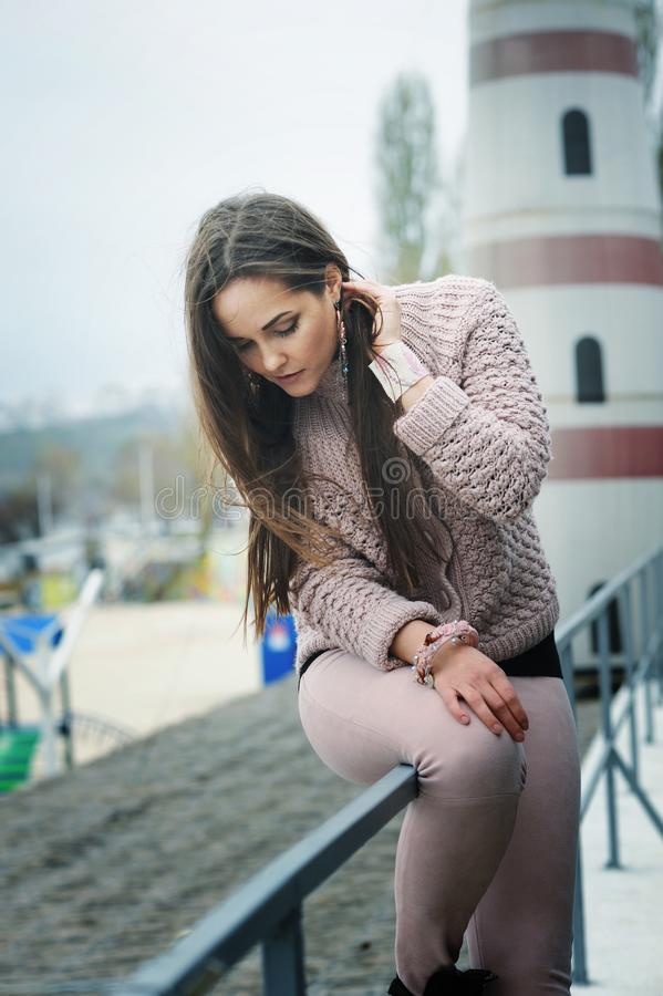El retrato feliz joven de la mujer, mirando abajo y sonriendo, se vistió en el suéter rosado apacible lindo, moda del otoño fotos de archivo libres de regalías
