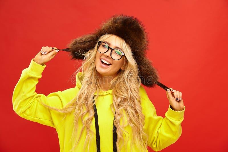El retrato femenino de la mujer feliz en sombrero con los earflaps, tiene un humor de la alegría, sonrisa sincera, soportes en fo imagenes de archivo