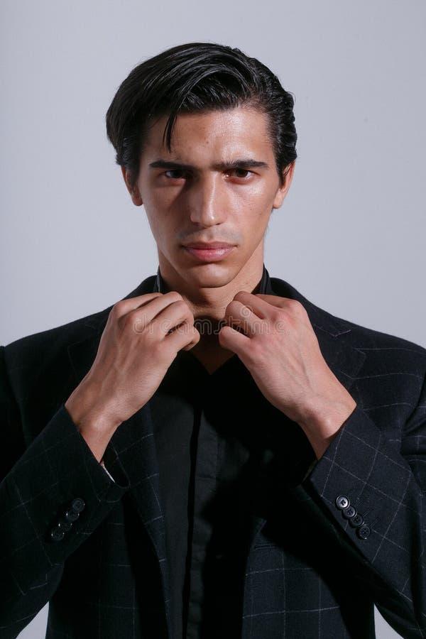 El retrato frontal del hombre joven hermoso en traje negro de los inspectores, arregla su cuello, aislado en un fondo blanco fotografía de archivo libre de regalías