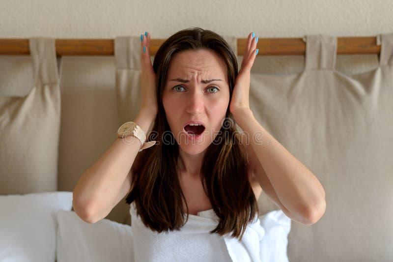 El retrato grande de una mujer que lleva a cabo su cabeza con sus manos, el concepto de dolor de cabeza, jaquecas, vecinos ruidos imagen de archivo