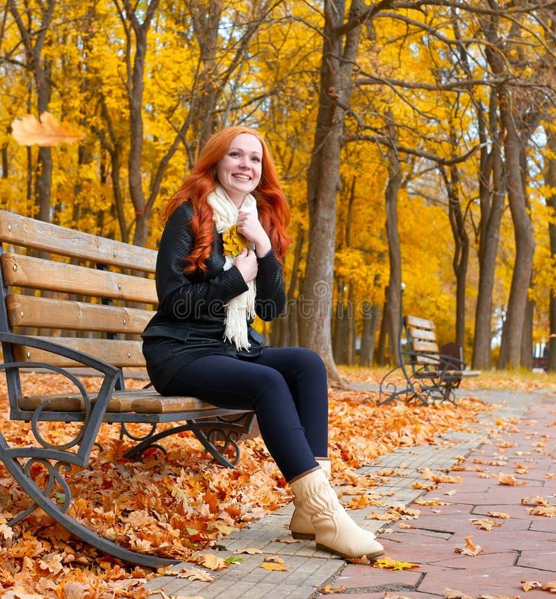 El retrato hermoso de la chica joven se sienta en banco en parque con la hoja amarilla a disposición, temporada de otoño, pelirro foto de archivo