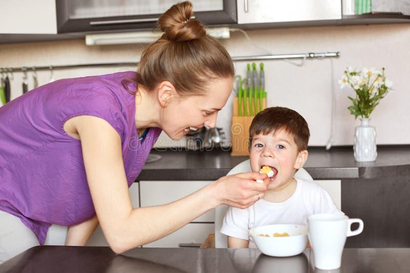 El retrato horizontal de la madre joven en el equipo casual, niño de las alimentaciones con la cuchara, le da la comida sana, tom imagenes de archivo