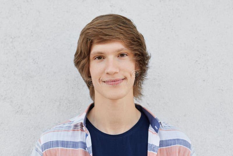 El retrato horizontal del adolescente masculino hermoso con los ojos oscuros, hoyuelos en mejillas, teniendo peinado de moda, cam imagen de archivo