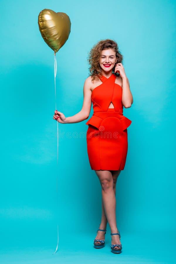 El retrato integral de una mujer joven de risa se vistió en el vestido rojo que sostenía el globo del corazón del aire mientras q imagenes de archivo
