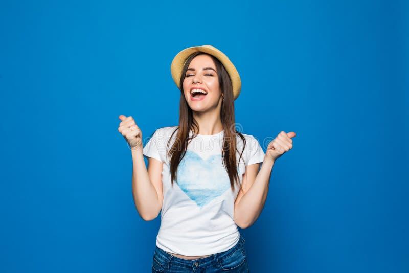 El retrato integral de una mujer joven satisfecha feliz del viajero en el sombrero de la playa que se coloca con las manos aument imagen de archivo libre de regalías