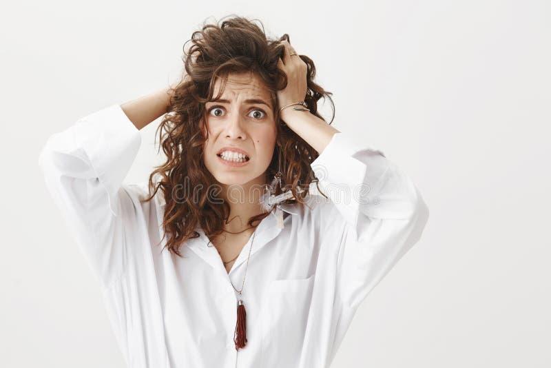 El retrato interior de la mujer ansiosa pasmada que no conocen qué hacer y del tener ataque de pánico, celebrando da en el pelo fotografía de archivo