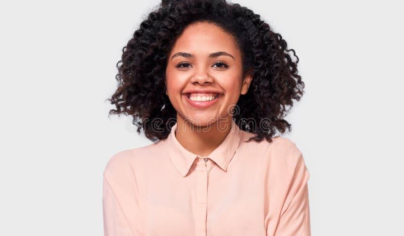 El retrato interior de la mujer joven afroamericana feliz, vestido en camisa beige casual, sonríe agradable en la cámara imagen de archivo