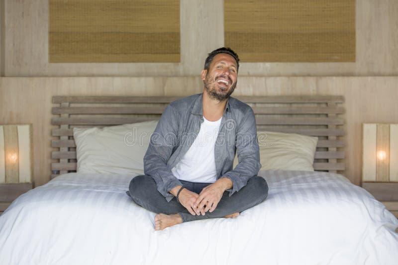 El retrato interior de 30s al hombre feliz y hermoso de 40s en casa en la camisa sport y los vaqueros que se sentaban en cama rel fotos de archivo libres de regalías