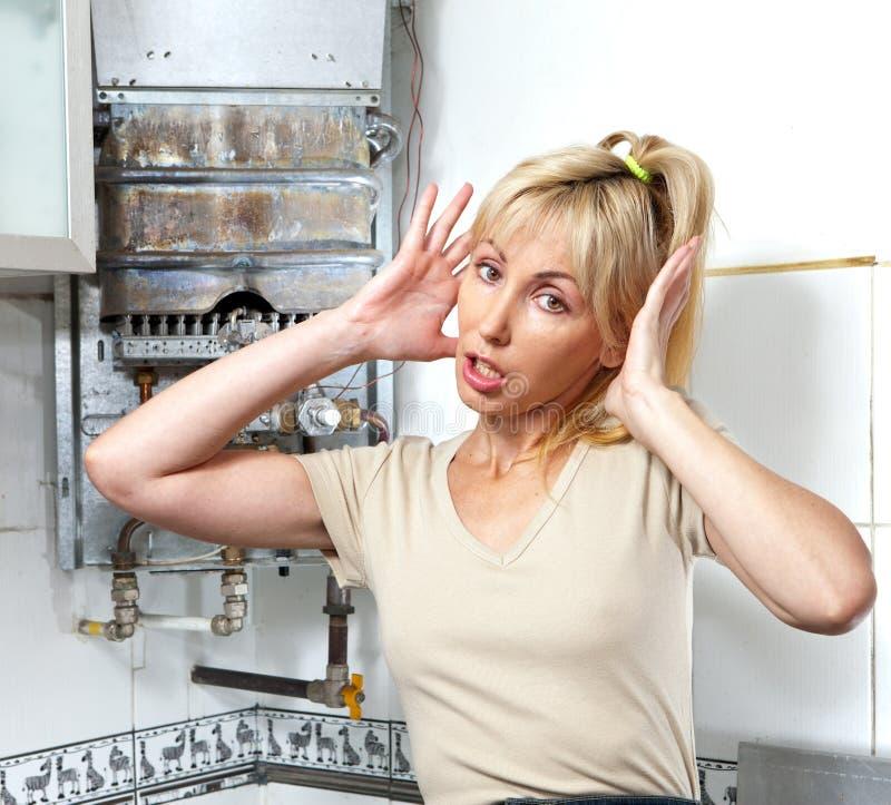 El retrato la mujer joven está trastornado por ése que el calentador de agua del gas se ha roto foto de archivo libre de regalías