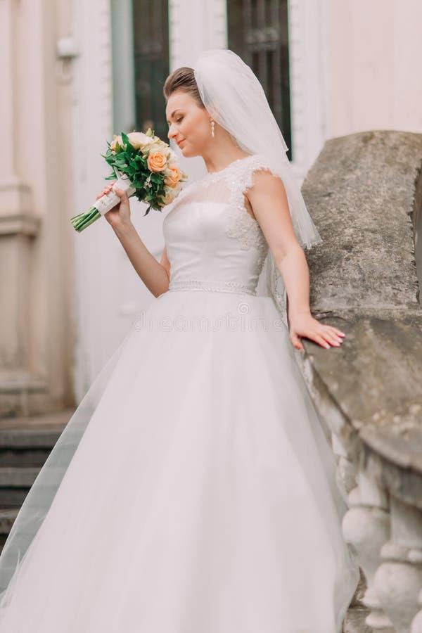 El retrato lateral sensible de la novia en el vestido largo que huele el ramo de flores amarillas fotografía de archivo libre de regalías