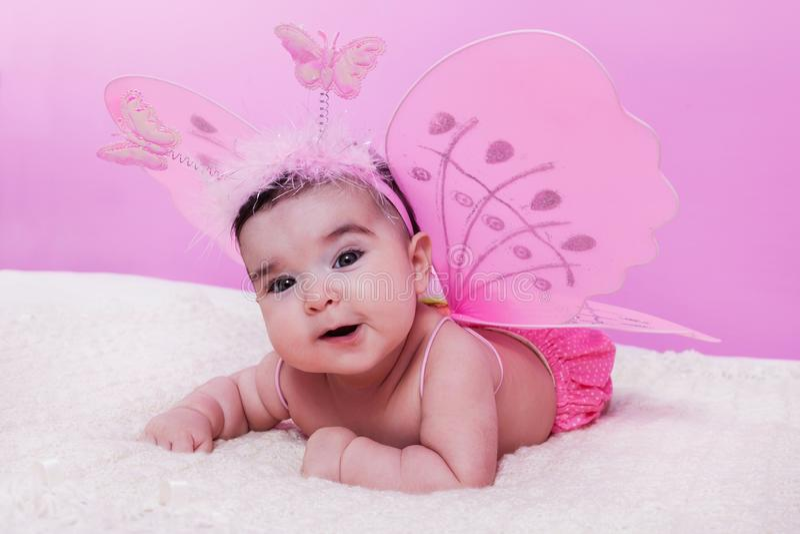El retrato lindo, bonito, feliz, rechoncho y sonriente del bebé, con la mariposa rosada se va volando fotografía de archivo libre de regalías