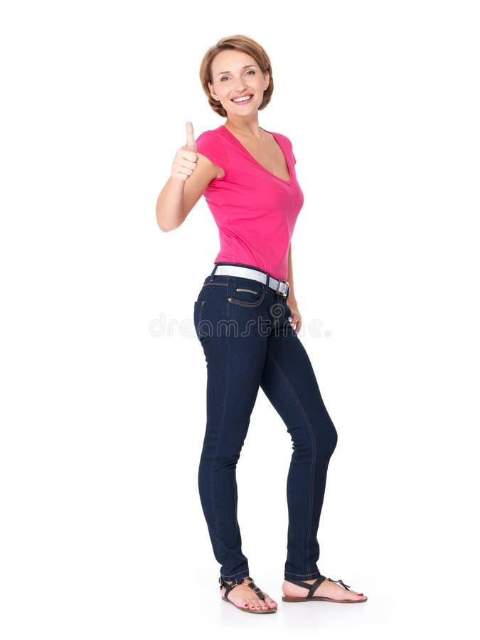El retrato lleno de una mujer feliz adulta con los pulgares sube la muestra imágenes de archivo libres de regalías