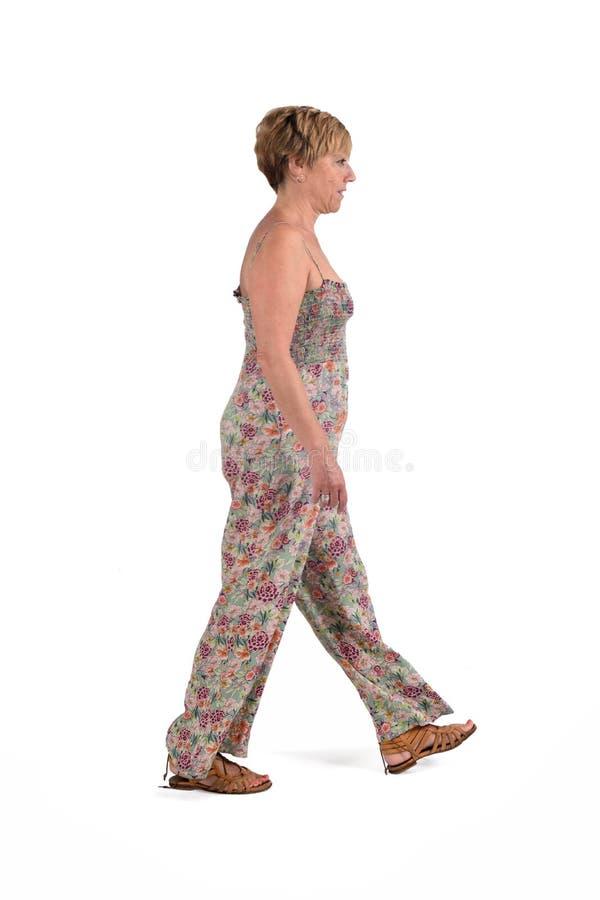 El retrato lleno del centro envejeció a la mujer que caminaba en blanco foto de archivo