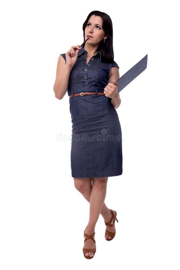 El retrato lleno del cuerpo de la mujer de negocios piensa en vestido con el tablero y la pluma, aislados en blanco imagen de archivo