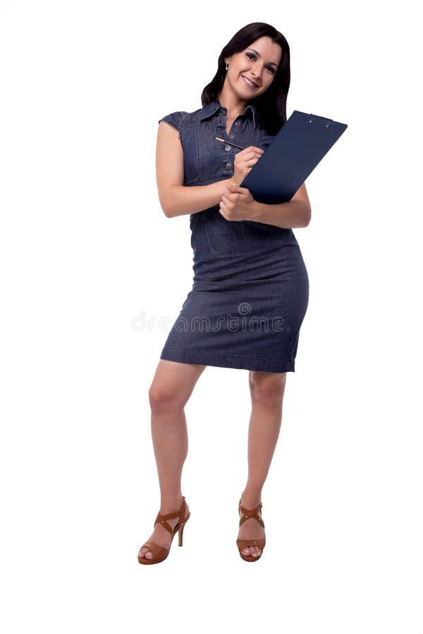 El retrato lleno del cuerpo de la mujer de negocios sonriente en vestido escribe con el tablero y la pluma, aislados en blanco fotografía de archivo