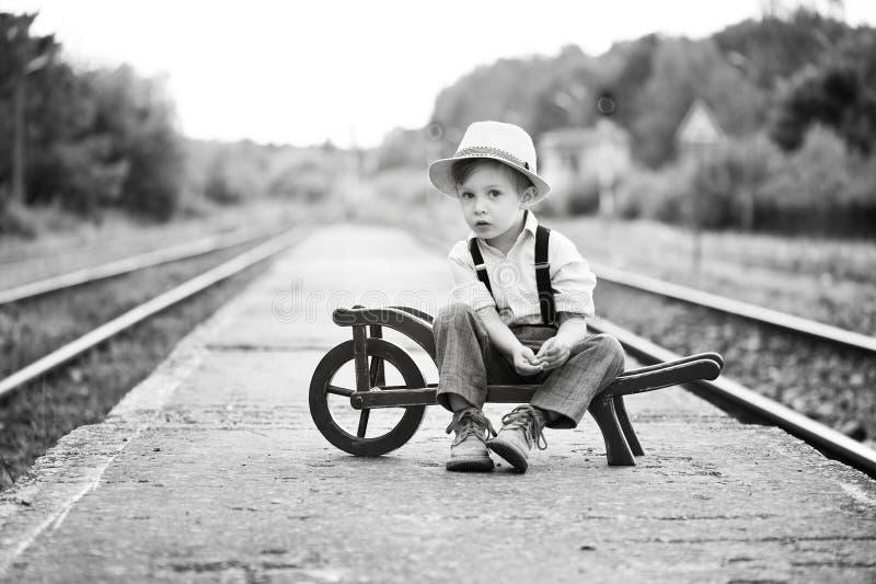 El retrato monocromático del muchacho lindo que lleva en el estilo retro que se sienta en el ferrocarril y está esperando algo foto de archivo