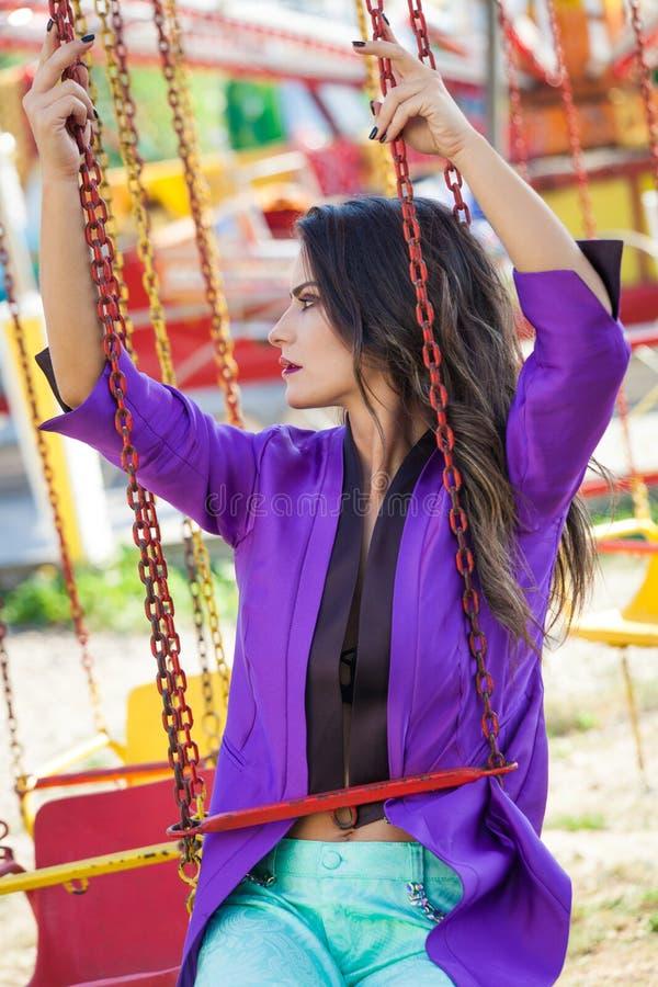 El retrato moreno caucásico de la mujer de la moda joven se sienta en el carrusel que vuela en verano del parque de atracciones imagen de archivo libre de regalías