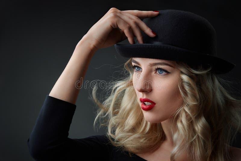 El retrato oscuro de la mujer rubia del encanto, llevando un sombrero, tiro del estudio, empañó el fondo, luz del día fotos de archivo