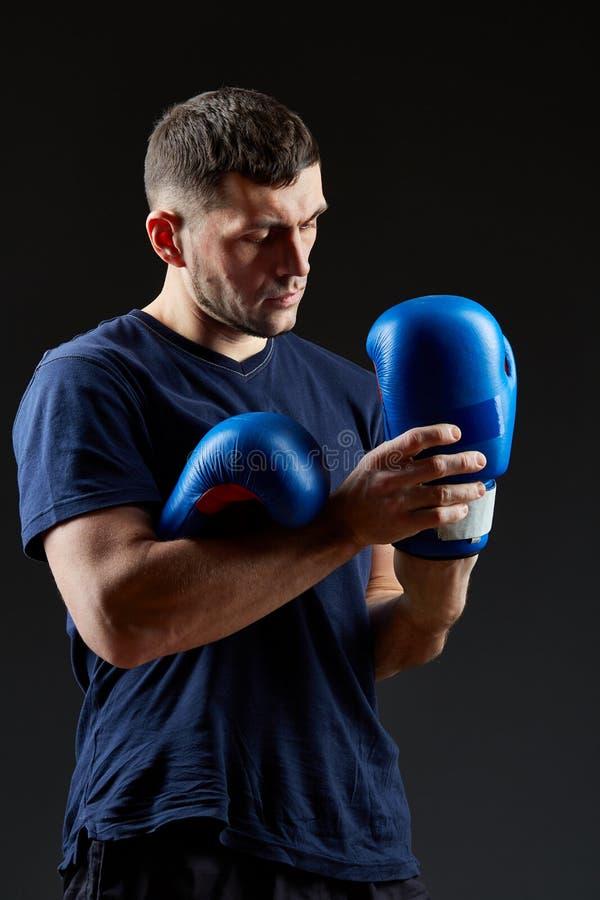 El retrato oscuro del estudio del combatiente muscular hermoso que se preparaba para encajonar en oscuridad empañó el fondo imagen de archivo