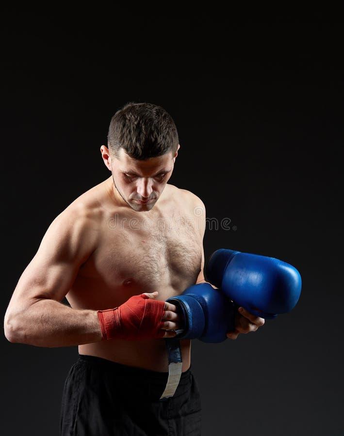 El retrato oscuro del estudio del encajonamiento practicante del combatiente muscular hermoso en oscuridad empañó el fondo imagen de archivo