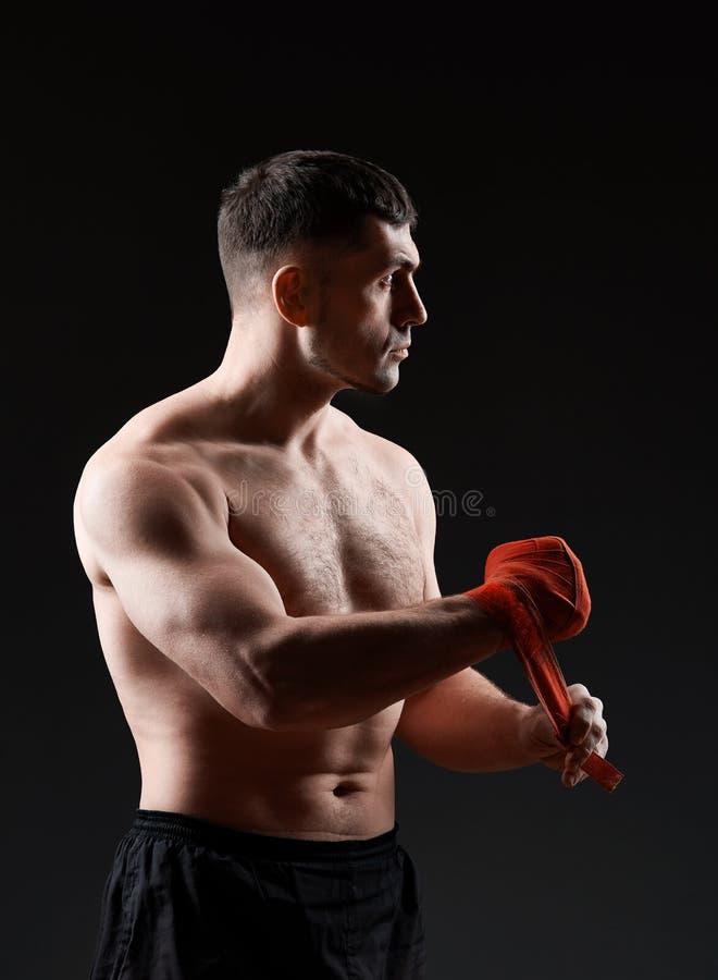El retrato oscuro del estudio del encajonamiento practicante del combatiente muscular hermoso en oscuridad empañó el fondo fotos de archivo libres de regalías