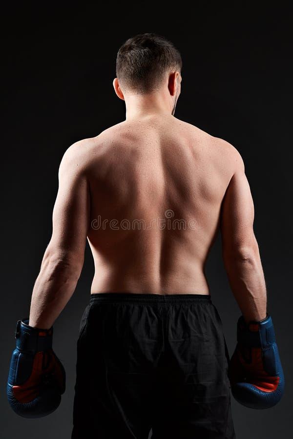 El retrato oscuro del estudio del encajonamiento practicante del combatiente muscular hermoso en oscuridad empañó el fondo fotos de archivo