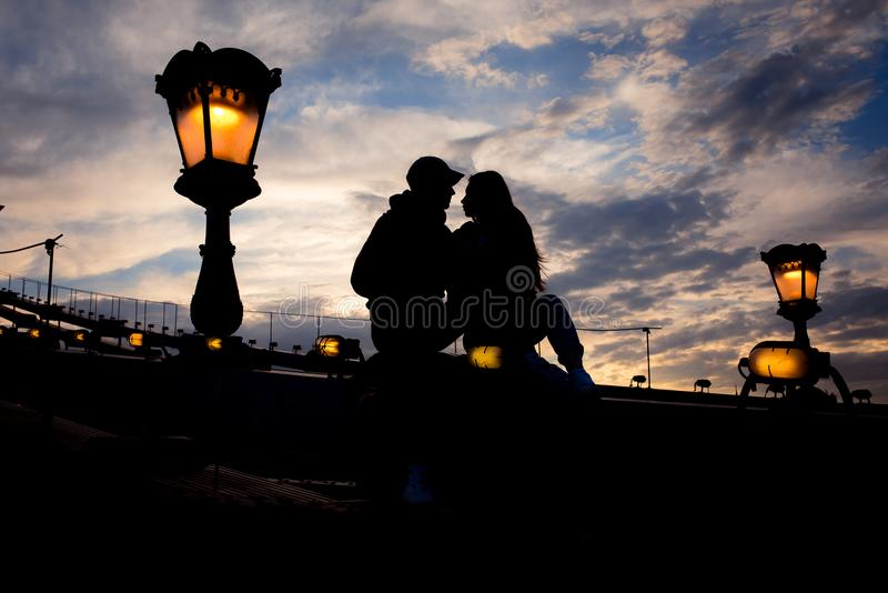 El retrato romántico de los pares cariñosos siluetea sentarse en el puente de cadena cerca de la lámpara de calle del relámpago e fotos de archivo