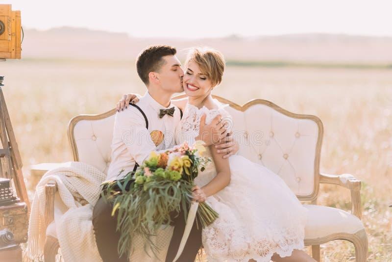 El retrato romántico del primer del novio que besa a la novia con el ramo en la mejilla en el campo soleado E imágenes de archivo libres de regalías