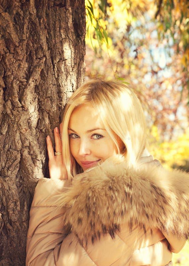 El retrato rubio sonriente de la mujer de los jóvenes, presentando en parque del otoño, se vistió en chaqueta con sudadera con ca foto de archivo libre de regalías