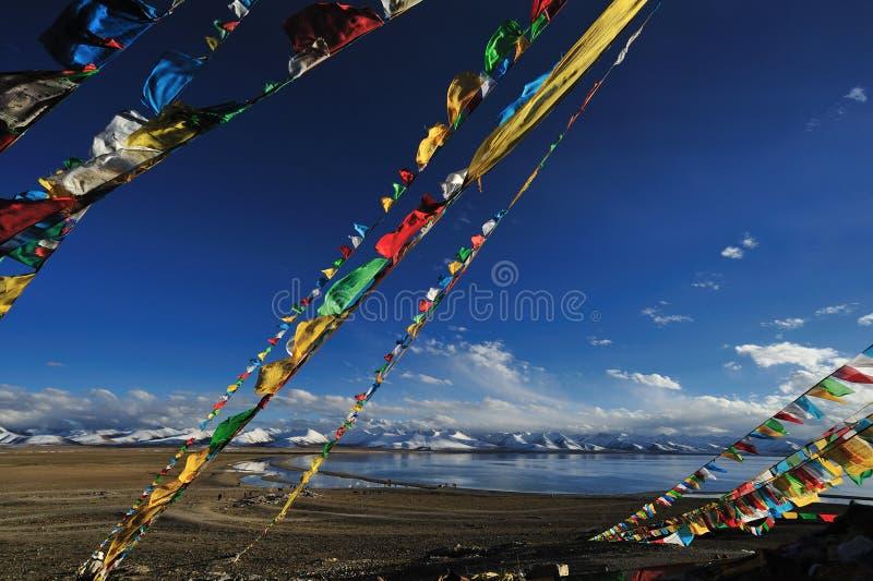 El rezo señala por medio de una bandera cerca del lago celeste Namtso fotografía de archivo