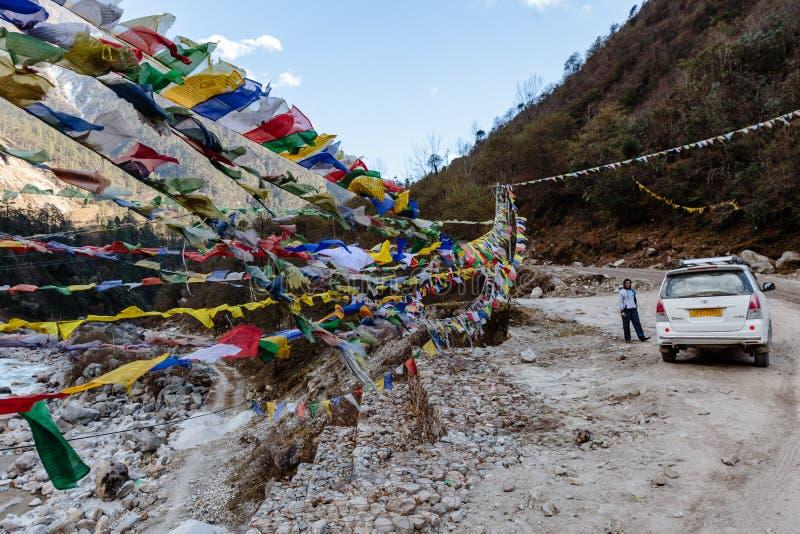 El rezo tibetano señala agitar por medio de una bandera y swaddled en sideway con el coche blanco sobre el río congelado en el va foto de archivo