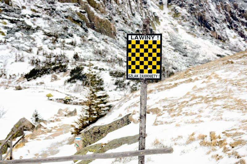 El riesgo negro y amarillo de la avalancha peligro señal adentro las montañas imagen de archivo libre de regalías