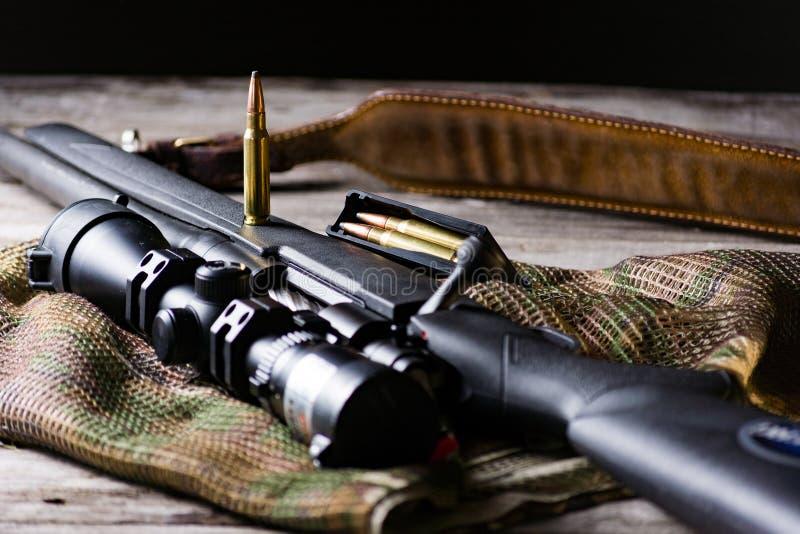 El rifle negro con la munición y alcance en el fondo del multicam Cierre para arriba imagenes de archivo