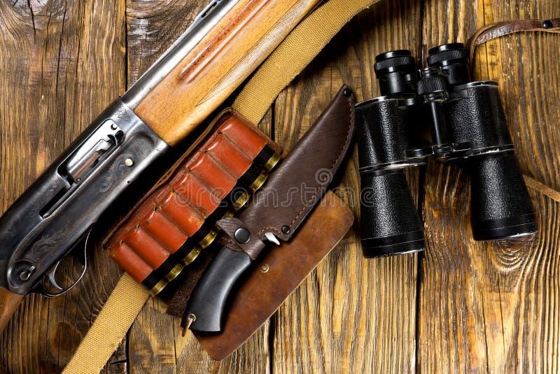 El rifle y la munición de la caza mienten en fondo de madera imagen de archivo