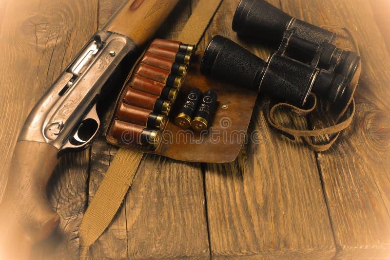 El rifle y la munición de la caza mienten en fondo de madera fotos de archivo libres de regalías