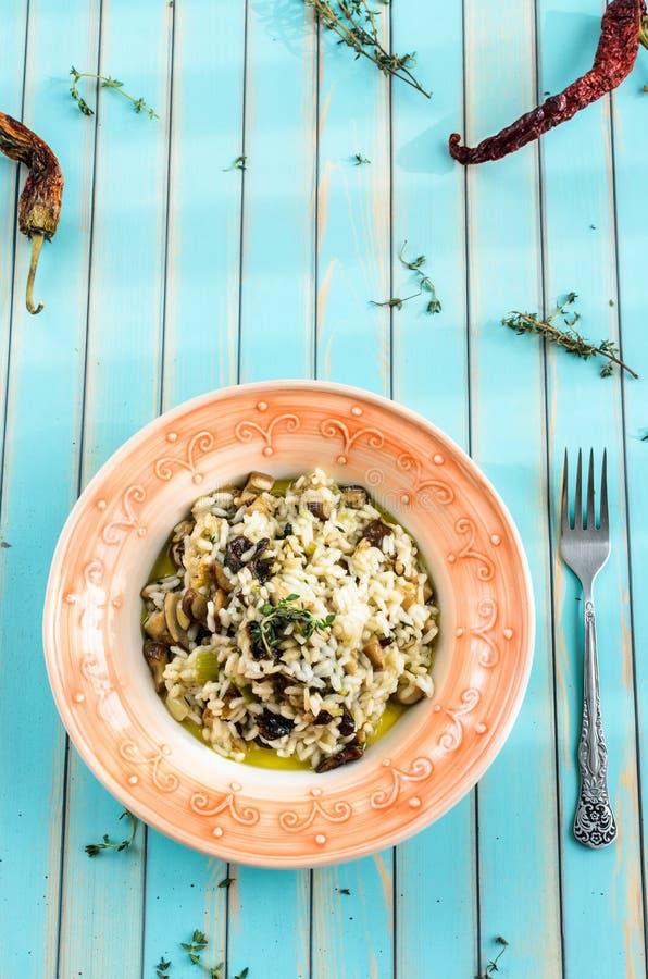 El risotto delicioso con porcini prolifera rápidamente sobre fondo de madera de la turquesa imagenes de archivo