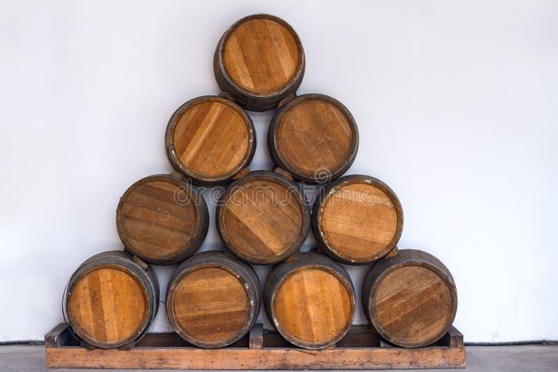 El roble barrels con el vino presentado en la forma de un triángulo en un fondo blanco imagen de archivo
