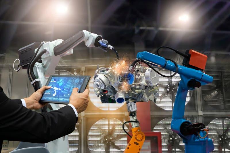 El robot de la automatización de control de la pantalla táctil del ingeniero del encargado arma la producción de los robots a de  fotografía de archivo libre de regalías