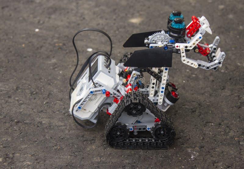 El robot de Lego se coloca en el asfalto fotografía de archivo