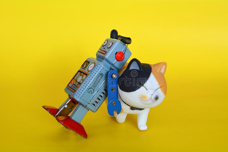 El robot del juguete de la lata del vintage y un gato aislaron fotos de archivo libres de regalías