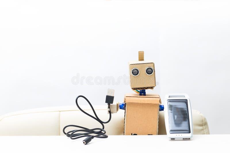 El robot sostiene a disposición una batería solar, alambre fondo blanco; fotografía de archivo