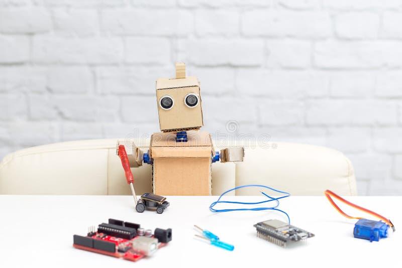 El robot sostiene un destornillador en su mano y recoge el machi foto de archivo