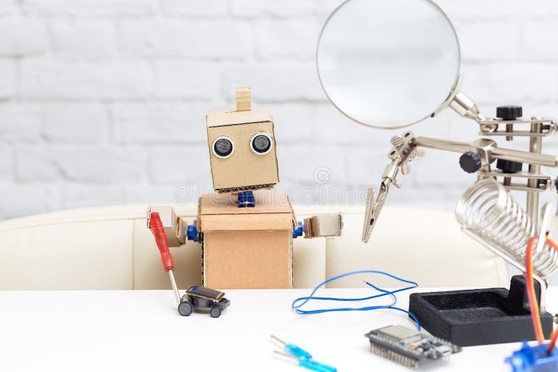 El robot sostiene un destornillador en su mano y recoge el machi fotos de archivo libres de regalías