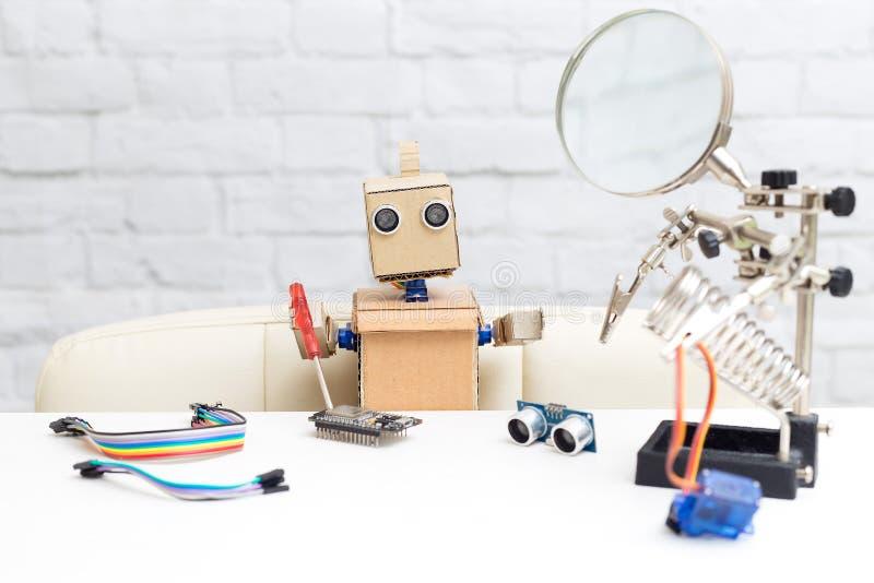 El robot sostiene un destornillador y recoge el microcircuito Nea fotos de archivo libres de regalías