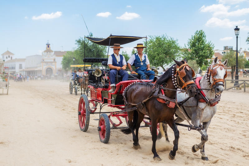 El ROCIO, ANDALUCIA, SPAIN - MAY 22: Carriage rides through the village after the religious procession. Son and father equestrians. 2015 The most famous stock photos