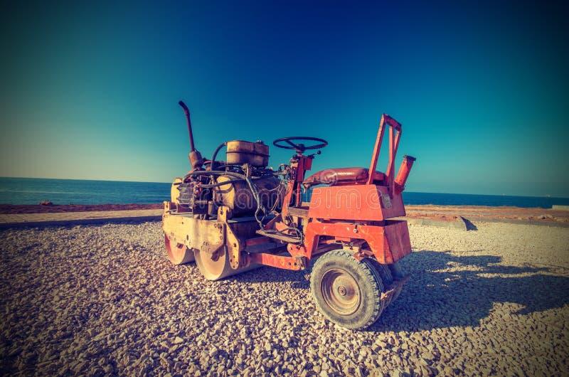 El rodillo viejo (pavimentadora) prepara la tierra para la colocación del asfalto imagenes de archivo