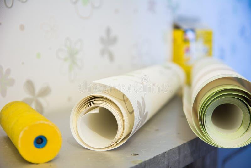 El rodillo y el vinilo de goma del papel pintado wallpaper para la reparación del sitio imagen de archivo libre de regalías