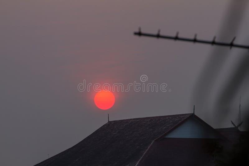 El rojo brillante del sol para arriba en la madrugada, sobre el tejado de la casa fotos de archivo libres de regalías
