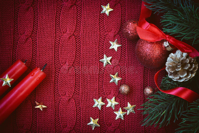 El rojo de la Navidad hizo punto el fondo con la bola en la cinta, dos velas imagen de archivo