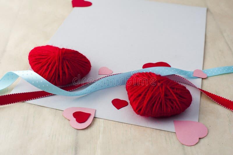 El rojo dos hizo punto corazones, cintas y la hoja blanca imágenes de archivo libres de regalías